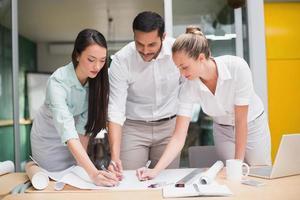 team di architettura che lavora insieme alla scrivania foto
