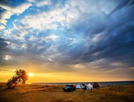 tenda e auto sulla riva del mare foto