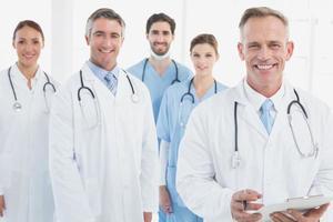 medici sorridenti tutti in piedi insieme foto