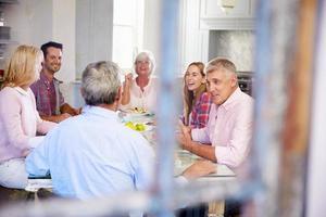 gruppo di amici che godono insieme del pasto a casa foto