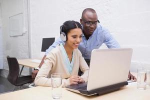 squadra di affari che lavora felicemente insieme sul computer portatile foto