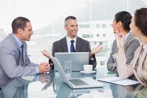 uomini d'affari sorridenti che lavorano insieme davanti a un caffè foto