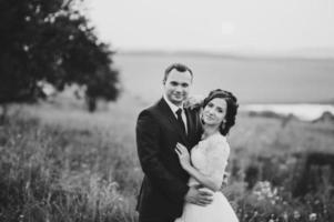 sposi insieme in posa durante il tramonto al campo estivo. foto