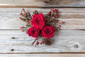 tre rose rosse raggruppate su sfondo di legno vecchio.