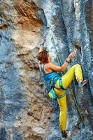scalatore arrampicata su una scogliera foto