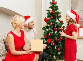 famiglia sorridente che decora l'albero di Natale foto