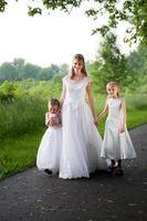 ragazze di fiore con la sposa matura che cammina giù la pista boscosa foto