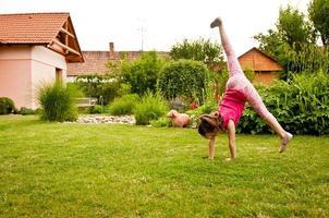 bambino che fa cartwheel nel cortile foto