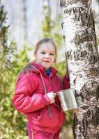 bambino raccoglie linfa di betulla nella foresta di primavera foto