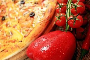 Pizza con sfondo rustico di verdure ed erbe foto