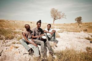 tre uomini africani che giocano a djembe nel prato