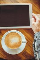 le mani degli uomini tengono il tablet con il caffè foto