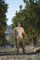 contadino in piedi in campo arancione foto