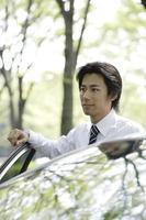 uomo d'affari in piedi sul lato auto foto