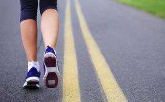 piedi femminili del corridore che corrono sulla strada foto