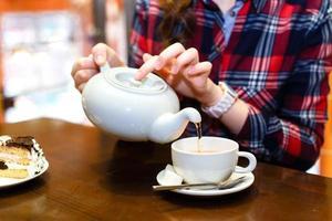 le mani femminili hanno versato il primo piano del tè verde foto