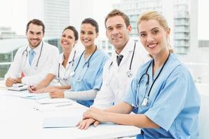 medici maschi e femmine seduti in fila foto