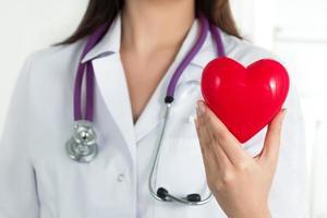mani del medico femminile che tengono cuore rosso foto