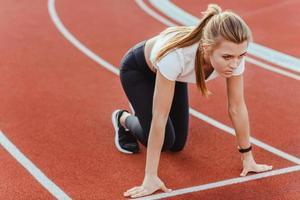 corridore femminile in piedi nella posizione iniziale foto