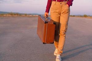 il viaggiatore va con una valigia foto