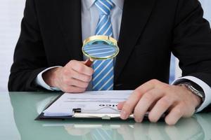 fattura d'esame dell'uomo d'affari tramite la lente d'ingrandimento foto