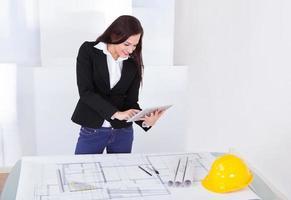 architetto con tavoletta digitale in piedi alla scrivania foto