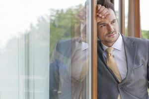 uomo d'affari premuroso che osserva via mentre si appoggia la porta di vetro