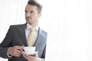 uomo d'affari con la tazza di caffè che osserva via in ufficio foto