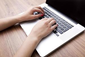 primo piano delle mani della donna di affari che per mezzo del computer portatile alla tabella foto