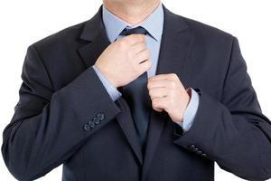primo piano di un uomo d'affari che adegua la sua cravatta foto