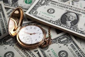 orologio d'oro e banconote da un dollaro foto
