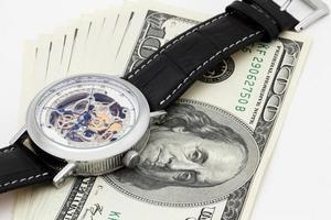 primo piano dell'orologio e dei soldi. il tempo è denaro concetto foto