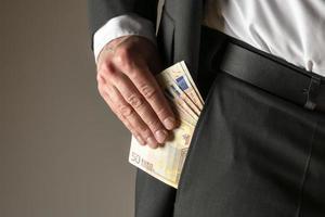 uomo d'affari mettendo i soldi in tasca foto