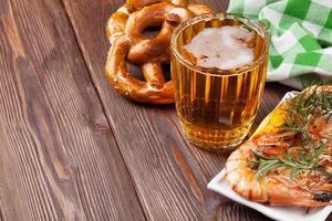 pretzel, boccale di birra e gamberi alla griglia foto