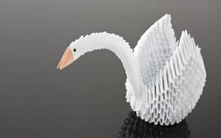 cigno bianco origami sulla superficie grigia foto