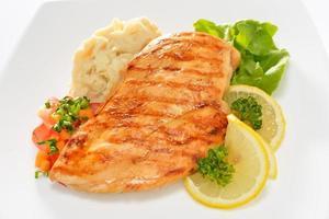 pollo alla griglia sul piatto con purè di patate e limone