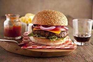 cheeseburger classico con cipolle, pomodori e sottaceti panino con semi di sesamo.