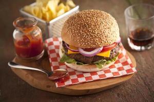 cipolle classiche cheeseburger, pomodoro e sottaceti panino ai semi di sesamo.
