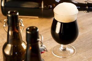 birra di vetro marrone, sul tavolo foto