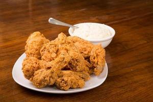 pollo fritto con cucchiaio in una ciotola di purè di patate foto