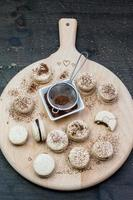 macarons fatti in casa con ganache ripieno su una superficie di legno foto