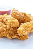strisce di pollo su bianco con salsa piccante foto