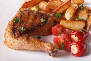 cosce di pollo alla griglia, patate fritte e primo piano di verdure.