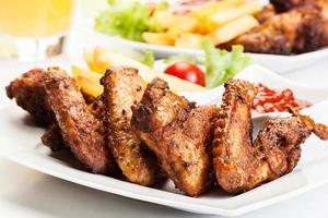 ali di pollo con patatine fritte e salsa piccante foto