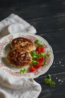 cotolette di maiale con insalata di verdure su superficie di legno scuro