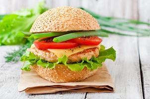 panino con hamburger di pollo, pomodori, formaggio e lattuga foto