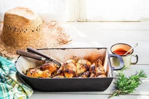 cosce di pollo calde con erbe e salsa in cucina estiva foto