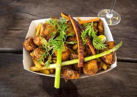 pesce e patatine fritte con carote, asparagi, fetta di limone