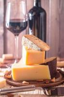 piatto di formaggi assortiti con vino rosso, noci e miele foto