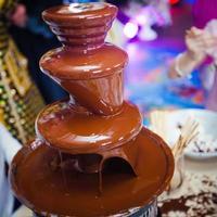 fontana di cioccolato con fonduta, frutta e marshmallow sulla festa dei bambini foto